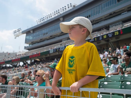 A young Rams fan watches a scrimmage on Sonny Lubick Field during an open house for CSU's new on-campus football stadium on Saturday, August 5, 2017. More than 10,000 Rams fans got their first look at the facility with a concessions and amenities in operation.
