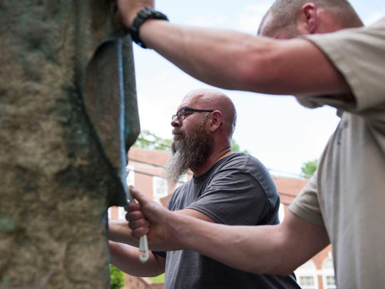 At center Phillip Cook of Powell, and to his right Norman Holliman of Maryville, scrub paint off a defaced Confederate monument in Fort Sanders Thursday, Aug. 17, 2017.