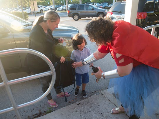 "Dr. Dianne Memmer-Novak (right), principal of Hobe Sound Elementary School, greets Renee Piccitto (left), and her son, kindergartner Vincenzo Piccitto, 5, as they arrive for the first day of school Tuesday, Aug. 15, 2017 in Hobe Sound. School staff wanted to do something special for the students, so they dressed as super heroes. ""Learning is our superpower,"" Dr. Memmer-Novak said. ""This is one of the best openings to school we've had yet."""