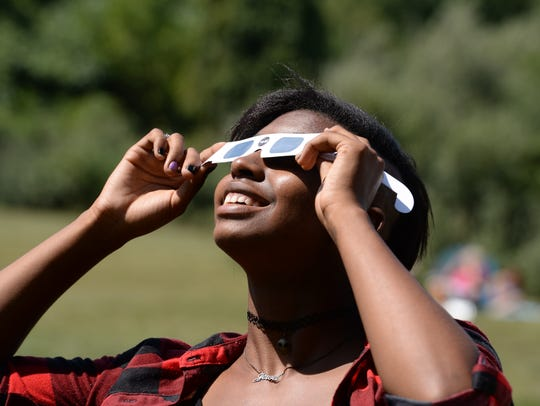 Jewel Peyton of Staunton uses safety glasses to watch