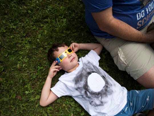 Landon Jenkins, 6, of Charleston, West Virginia puts his solar viewing glasses on while waiting for a total solar eclipse in Great Smoky Mountains National Park at Clingman's Dome Tuesday, Aug. 21, 2017.