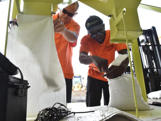 Robert Dale (left) and Ronald Taylor, of the City of Fort Pierce Public Works Department, make sand bags at the public works compound on Tuesday, Sept. 5, for the city to use to protect their facilities from Hurricane Irma damage. Currently the city is not making sandbags for the general public.