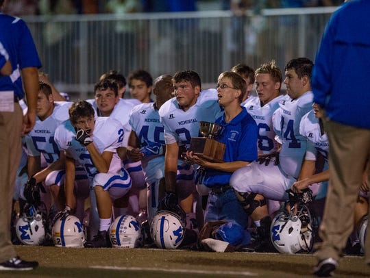 Memorial players listen to coach John Hurley after defeating Mater Dei last year. The winning team will again receive the Hunger Bowl trophy.