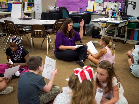 Jennifer Payne sits with Avery Lynn as they share work from a brainstorming activity at Daniel Wertz Elementary School in Evansville, Ind., on Thursday, Aug. 31, 2017.