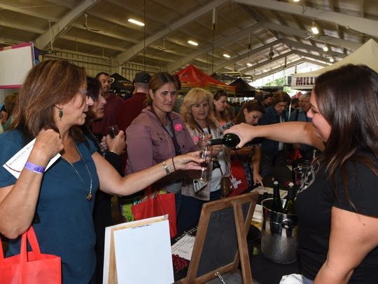 Kiersten Craig, right, tasting room associate at Robibero Winery in New Paltz, pours samplings of wine at a past Hudson Valley Wine and Food Festival in Rhinebeck. The annual event is set for this weekend at the fairgrounds.