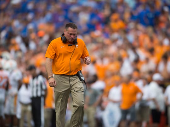 Vols coach Butch Jones walks toward an injured player