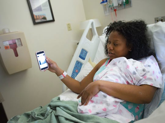 Tara Stoutt holds her one-day-old daughter, Saniyah, as she follows updates from her phone on the conditions of her home on the island of Tortola from her room at Poudre Valley Hospital on Tuesday, September 19, 2017. Stoutt evacuated from her home in the British Virgin Islands after Hurricane Irma to give birth in Fort Collins.