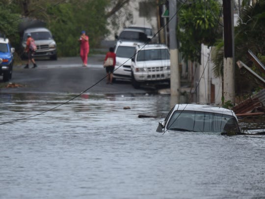 A car is stuck in a flooded street in in San Juan,