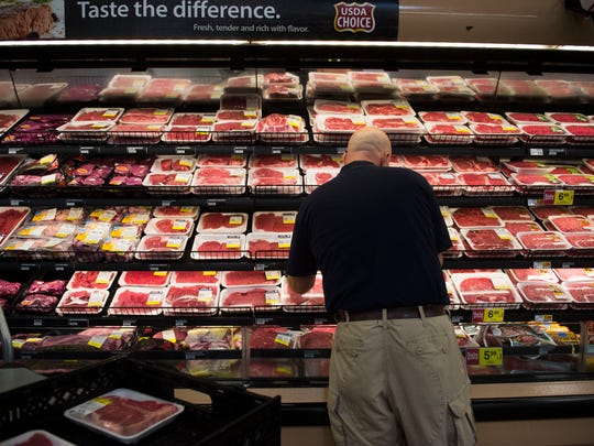 Kroger meat manager Alan Muncey demonstrates how employees sort through meats to be donated to Second Harvest food bank at the Farragut Kroger Marketplace in West Knoxville Thursday, Sept. 22, 2017.