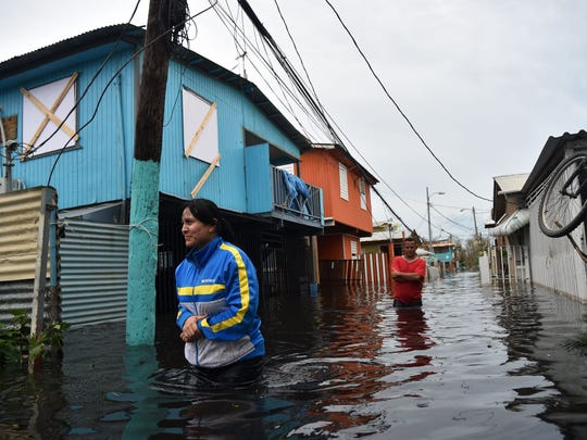 Residents cross a flooded street in Juana Matos, Puerto