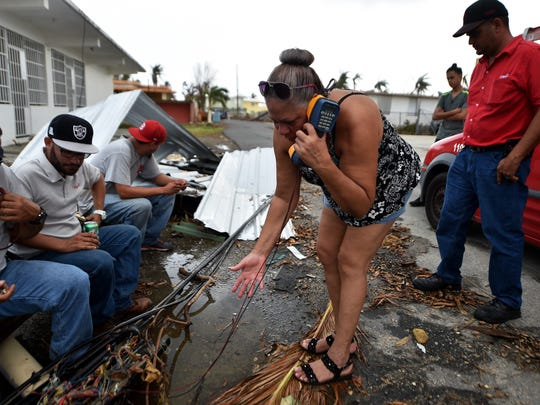 A woman tries to talk with her family to say that she is good condition while telephone technicians try to repaire the lines in Punta Santiago, Humacao, in the east of Puerto Rico, on September 27, 2017, one week after the passage of Hurricane Maria. The US island territory, working without electricity, is struggling to dig out and clean up from its disastrous brush with the hurricane, blamed for at least 33 deaths across the Caribbean.