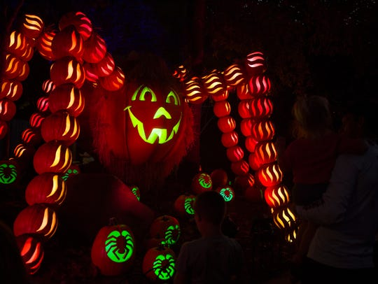 Dollywood attendees check out a pumpkin spider at Dollywood's nighttime fall experience, Great Pumpkin LumiNights, on Sept. 28, 2017.