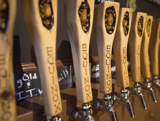 Taps line the wall behind the bar Equinox Brewing on