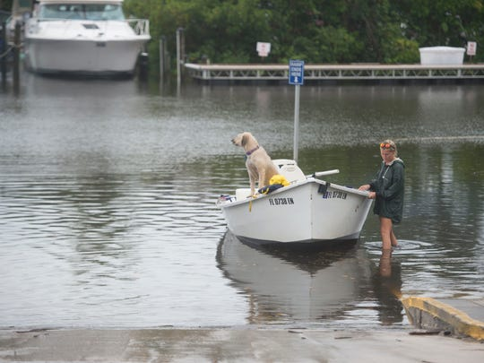 """Heather Hall, of Stuart, waits to board a boat from a flooded dock at Shepard Park on Thursday, Oct. 5, 2017, in Stuart. Despite the high """"king"""" tide, partly caused by strong winds and October's full moon, and rainy conditions, Hall and her family, Ty Hoza, Izzy Hoza, 2, (not pictured), and Maka the dog, boated out into the St. Lucie River. """"It'll be kind of fun, actually,"""" Hall said."""