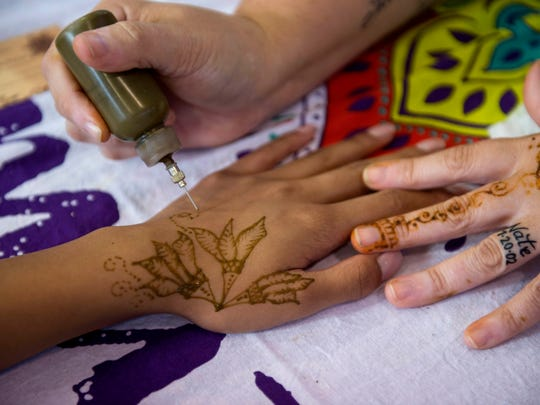 Sarah Dotson draws henna on Martina Catalan, of the Philippines, during the USI Global Crossroads festival at Ribeyre Auditorium in New Harmony, Ind., on Saturday, Oct. 14, 2017.