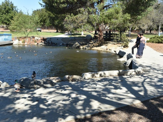 Mathew and Paris Sier, of Thousand Oaks, watch as ducks cool off in a pond at Conejo Creek Park on Tuesday as temperatures in the county reached record highs for a second day in a row.