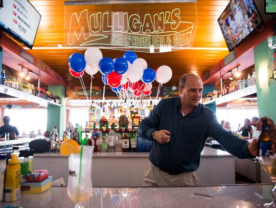 Stuart Mayor Troy McDonald serves behind the bar at