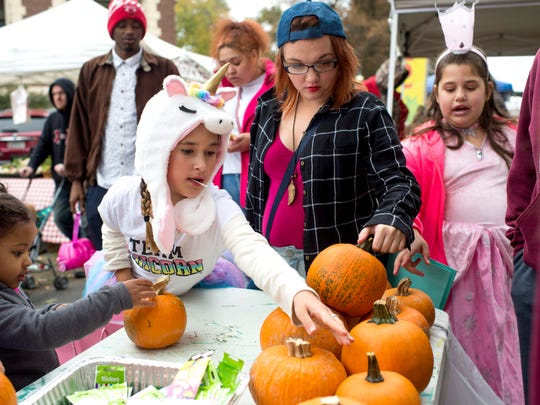 Sophie Smith, 9, dressed as a unicorn, picks out her pumpkin during Halloween on Franklin at the West Branch Library in Evansville, Ind., on Saturday, Oct. 28, 2017.