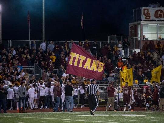 Titans students wave a flag as the Gibson Southern Titans take on the Memorial Tigers at Gibson Southern High School in Fort Branch, Ind., on Friday, Nov. 3, 2017. Memorial won 26-17 to claim the Class 3A Sectional 32 championship title.