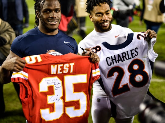 Running back Charcandrick West of the Kansas City Chiefs and running back Jamaal Charles of the Denver Broncos exchange jerseys following the game at Arrowhead Stadium on October 30 in Kansas City, Missouri.