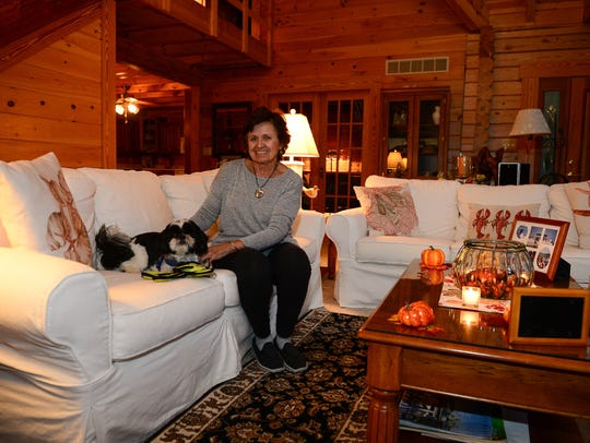 "Barbara ""Bobbi"" McClay sits on her couch with her dog"