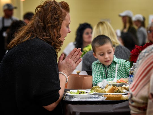 Jamie Laws prays before she and her son Landon Burchell eat lunch during the Thanksgiving banquet at the Nashville Rescue Mission on Nov. 22, 2017.