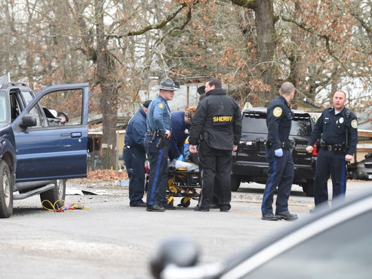 Medical personnel tend to alleged shooter Robert Dean Penny as law enforcement officers investigate Tuesday morning at the scene of a fatal shooting on Old Military Road.