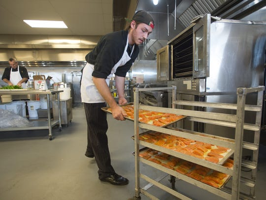 Peter Rosis tosses pans of salmon filets in the oven