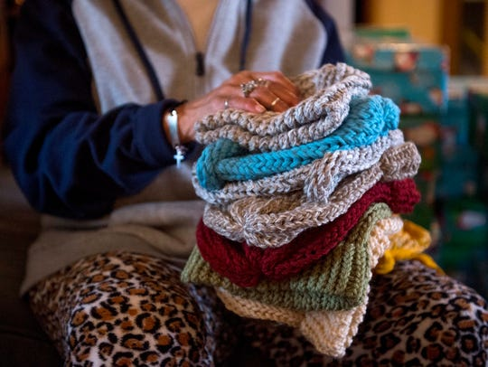 Phyllis Brown holds a stack of donated hats at the