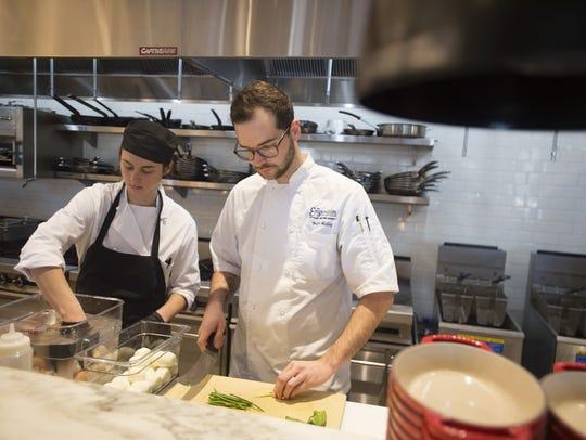 Victoria Glebe and Brett Hailey work in the kitchen