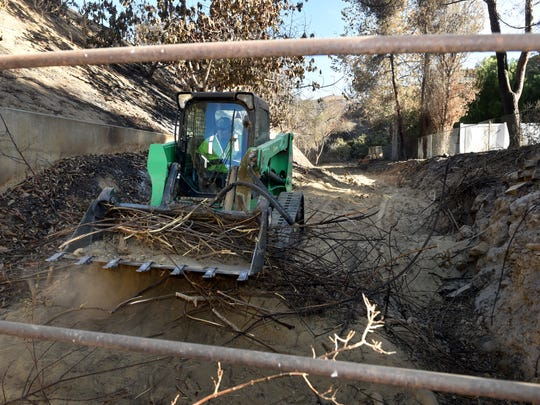 Doug Legan, of Fillmore, uses a Bobcat to remove charred and broken debris  from Sanjon Barranca near Buena Vista Street in Ventura on Thursday as the Ventura County Public Works Department clears the area after the Thomas Fire.