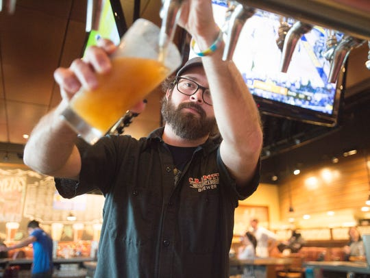 Head Brewer Jeff Eaton pours a pint of beer from the