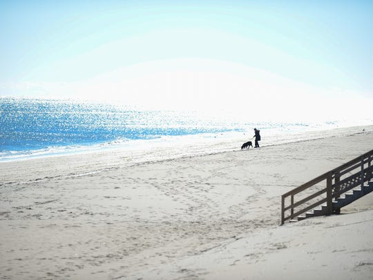 A file photo of a woman walking her dog on the beach. Bethany officials say it's an increasing problem on the boardwalk as residents complain dog owners not cleaning up after their pets.