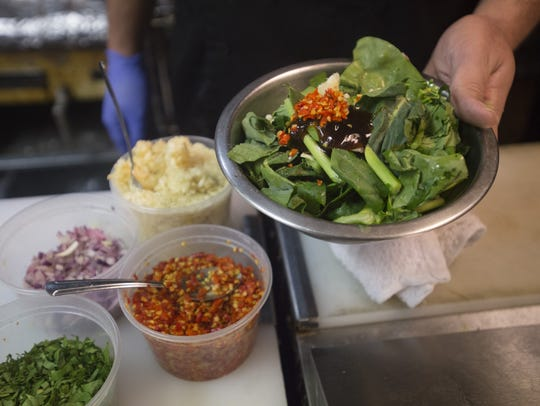 Spices are added to a dish of Chinese broccoli at Cafe
