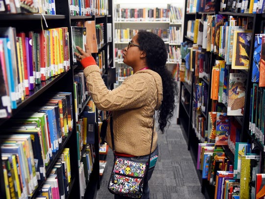 "T'Pring Asencio looks through the stacks of books at the newly reopened Gifford Library on Jan. 18, inside the Gifford Youth Achievement Center. The library suffered water damage and mold from Hurricane Irma and had to be closed for several months. ""The good thing about our reopening is that this is no longer just a children's collection, it is now multigenerational,"" said Tanya Huff, assistant library director."