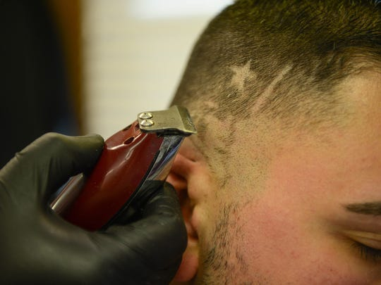 Paul Cusimano, Millville Barbershop Co-Owner, gets a Super Bowl LII themed custom hair cut by Barber Victor Hernandez on Thursday, Jan. 25, 2018.