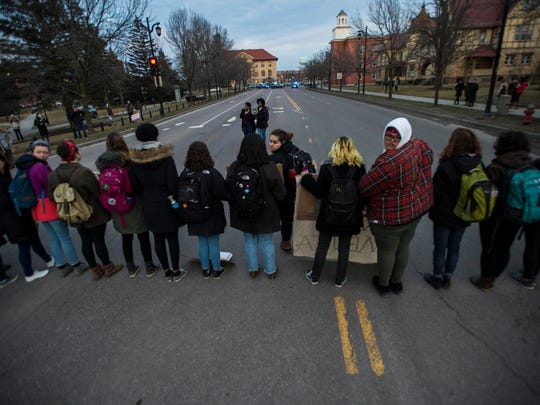 Protesters form a line across Main Street, closing down the road at the intersection of South Prospect Street at the height of the evening commute in Burlington on Thursday, Feb. 22, 2018, demanding action by University of Vermont President Tom Sullivan on what they say are dangerous and degrading conditions for students of color on campus.