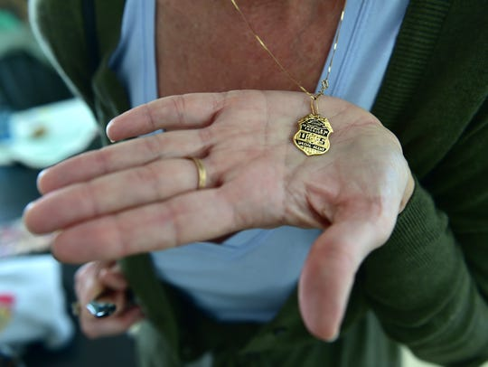 Kelley Williams holds a necklace pendant from the U.S. Department of the Treasury special agent shield given to her family following the death of her brother Robert J. Williams who was killed in the line of duty 25 years ago. He died on the first day of the standoff with David Koresh (aka David Wayne Howell) and Branch Davidian members.