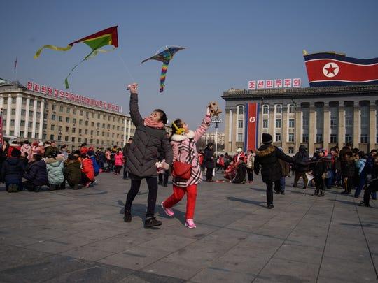 Children fly kites during Lunar New Year festivities