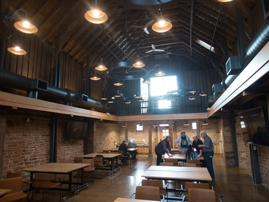 Family members and Woodward officials explore the renovated Coy Barn on Woodward's campus in Fort Collins on Wednesday. The barn, built in 1866, has been restored into a conference center.