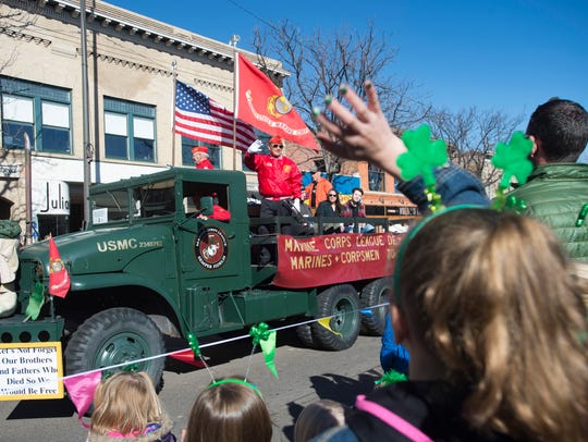 People wave as floats turn onto College Avenue during