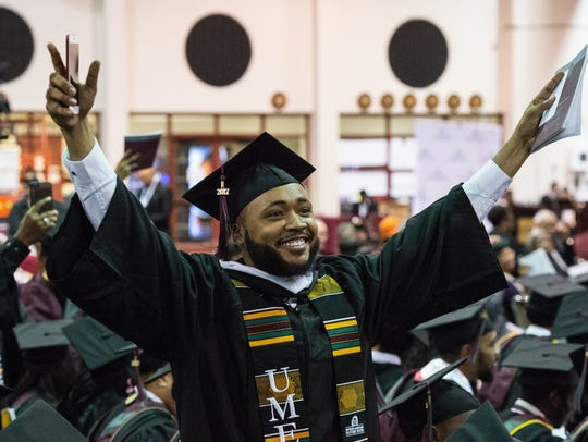 A graduate waves to family members in the audience