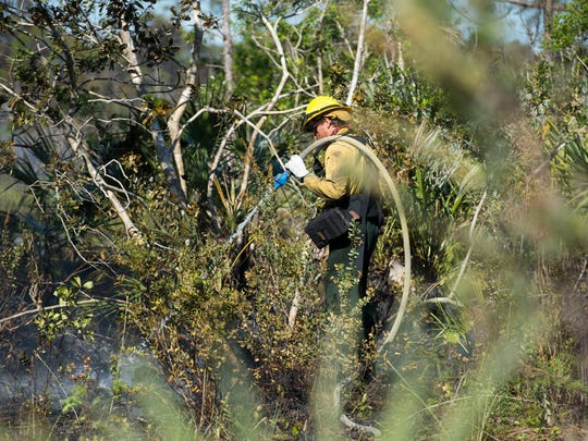 """AmeriCorps member Aaron Hochberg mops up a wildfire caused by a lightning storm earlier in the week, termed the Palma Wildfire, on March 22, 2018, north of Palm City in St. Lucie County. Relative humidity is supposed to drop, but winds will increase, which could cause the fire to spread toward Becker Road. """"We're going to do everything we possibly can to stop that,"""" said Mellisa Yunas, Florida Forest Service spokeswoman. """"You can plan but you can't predict weather."""""""