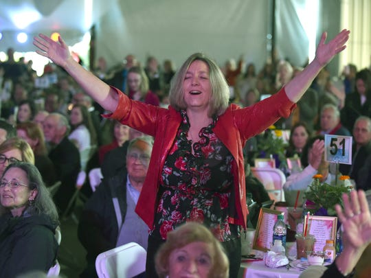 """Juelie Perry, of Sebastian, raises her hands in praise as special guest Guy Penrod sings during the 14th annual Vero Beach Prayer Breakfast Thursday, March 22, 2018, at the Indian River County fairgrounds. """"It is an amazing blessing to be in the presence of so many like-minded people,"""" Perry said. """"I'm here because I believe in community, being a business owner in the community, to come together to put Jesus as the center of our community."""" To see more photos, go to TCPalm.com."""
