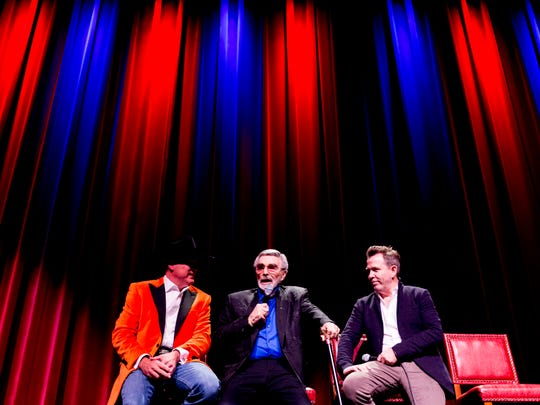 Burt Reynolds speaks on stage with movie producer and