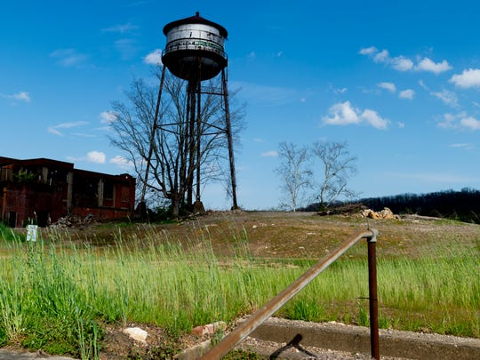 An old water tower stands beside one of the last remaining buildings and an empty plot of land at the former Magnet Mills site in Clinton, Tennessee.