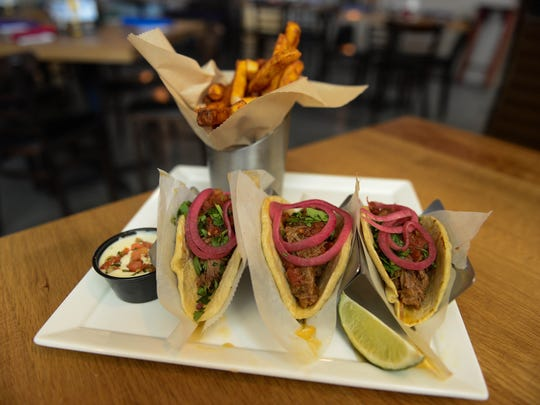 Bayside Cantina's Barbacoa taco's- slow roasted beef, pickled red onion, cilantro, roasted tomato and serrano sauce. Served with chili-dusted fries & queso. Tuesday, May 1, 2018.