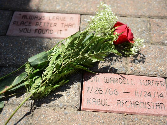 Roses lay on the newly installed bricks that have been