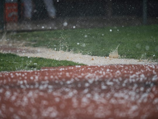 Hail splashes in puddles of rain during a weather delay
