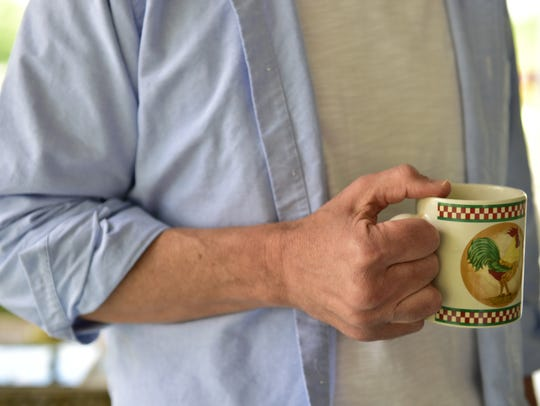U.S. Senate candidate Howard Sherman holds a cup coffee on the porch of his home in Meridian.